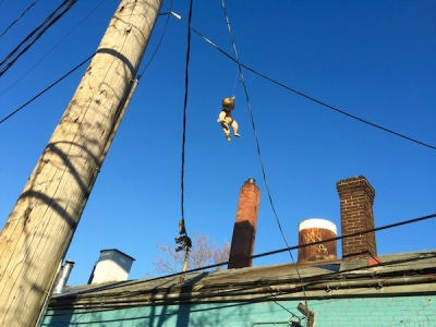 golden baby hanging from electric line over brick building, Pittsburgh, PA