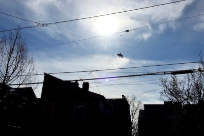 silhouette of baby doll dangling from electric line over row houses, Pittsburgh, PA