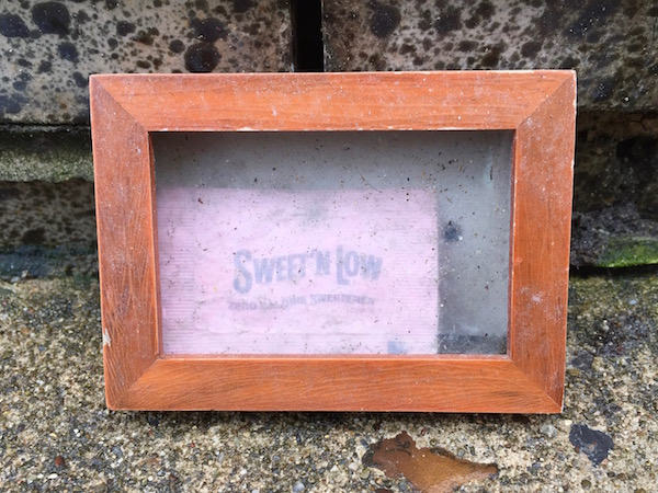 Tiny wooden picture frame containing a Sweet'n'Low packet