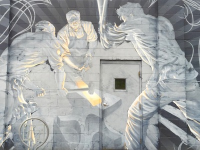 Mural painted on cinderblock wall of iron workers hammering hot steel on an anvil, Red Star Iron Works, Millvale, PA