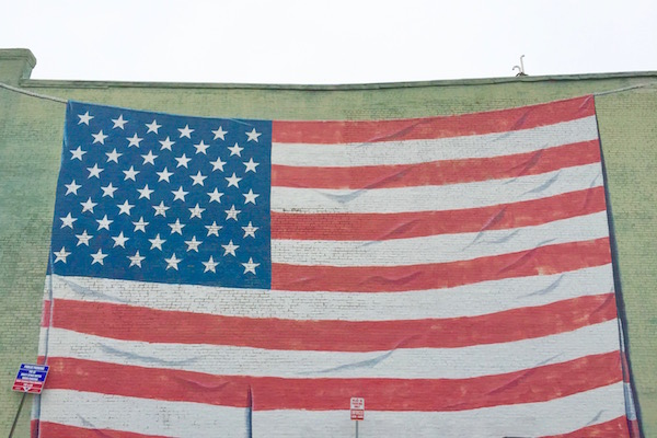 mural of American flag painted on exterior brick wall