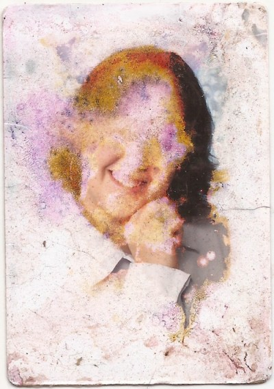 water-damaged wallet size photograph of an unknown woman