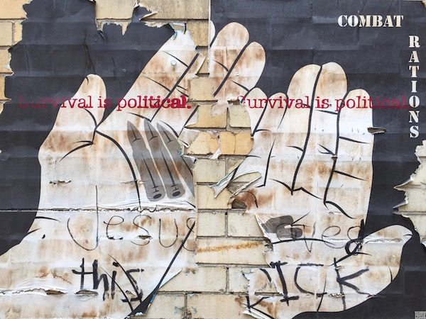 """wheatpaste poster of bare hands holding bullets and pills with the text """"Survival is political"""" and """"Combat rations"""", Pittsburgh, PA"""