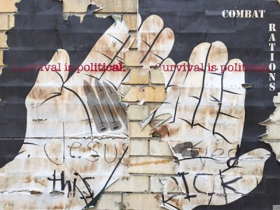 "wheatpaste poster of bare hands holding bullets and pills with the text ""Survival is political"" and ""Combat rations"", Pittsburgh, PA"