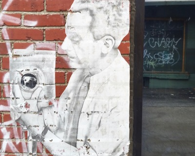 image of man with camera wheatpasted to brick wall, Pittsburgh, PA