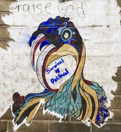 "wheatpaste poster of psychedelic eagle with graffiti ""Praise God"" and ""Survival is Political"", Pittsburgh, PA"