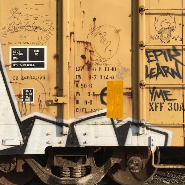 yellow boxcar with graffiti of a mountain range