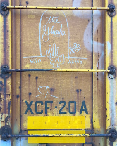 """detail of boxcar with graffiti of grave stone with message """"The Ghouls"""""""