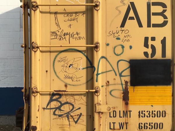 yellow boxcar with graffiti of a cartoon man smoking cigarette