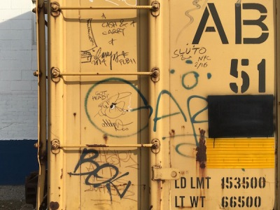 yellow boxcar with graffiti of a cartoon man smoking cigarette