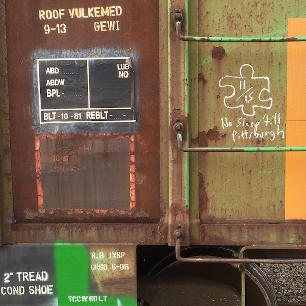 """detail of boxcar with graffiti of puzzle piece reading """"No sleep till Pittsburgh"""""""