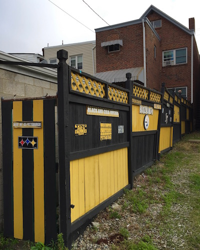 row house back yard fence painted black and gold and decorated with Steelers signs, Pittsburgh, PA
