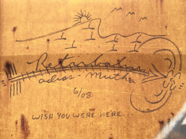 """boxcar graffiti of mountain, sunrise, and train tracks with text """"Retribalize, adios-mutha, wish you were here 6/08"""""""