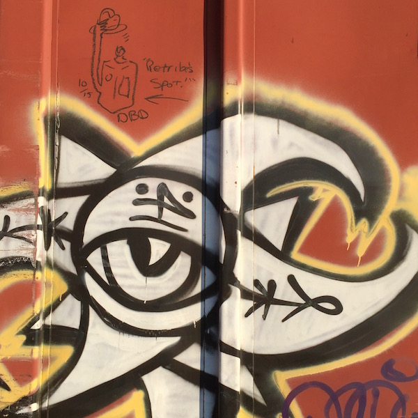 """boxcar graffiti of a jug with a hat and the message """"Retribe's spot!"""""""
