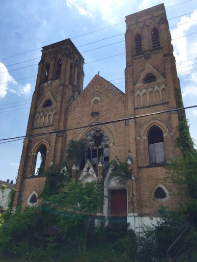 exterior of former Holy Trinity Catholic church, Duquesne, PA missing windows and trees growing over front steps