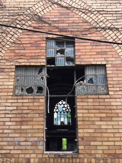 view through broken glass block window in shape of a cross to dark interior of former Holy Trinity Catholic church, Duquesne, PA
