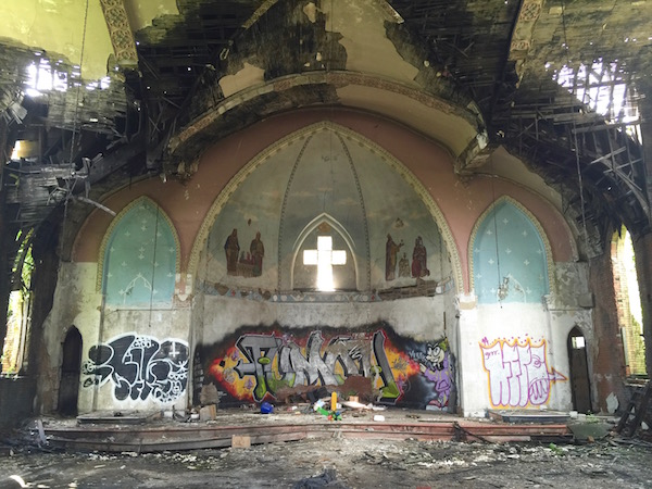 interior of former Holy Trinity Catholic church with spray paint graffiti and sky visible through the roof, Duquesne, PA