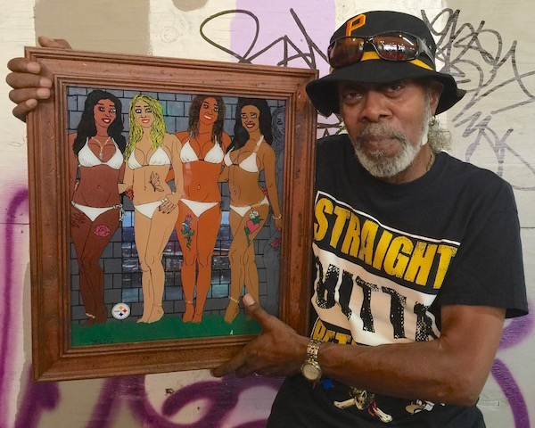 Artist JR Holtz holding a painting of four women in bikinis