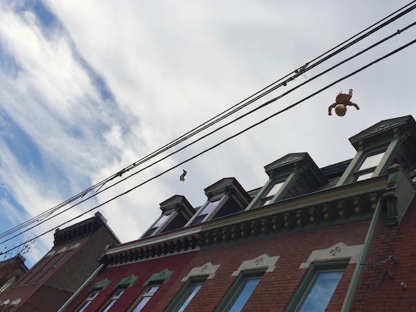 golden baby and baby foot hanging from wires in front of row houses, Pittsburgh, PA