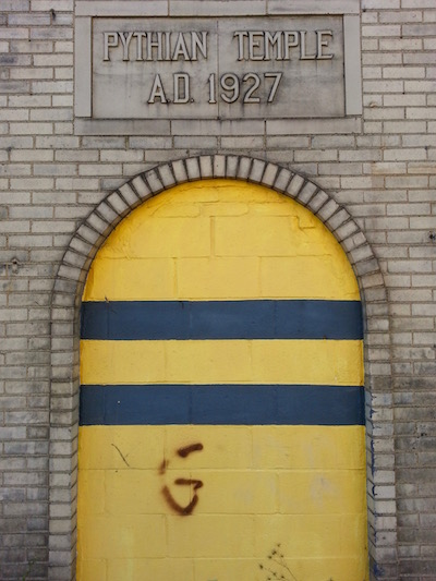 brick building with cinderblock doorway painted black and gold, Pittsburgh, PA
