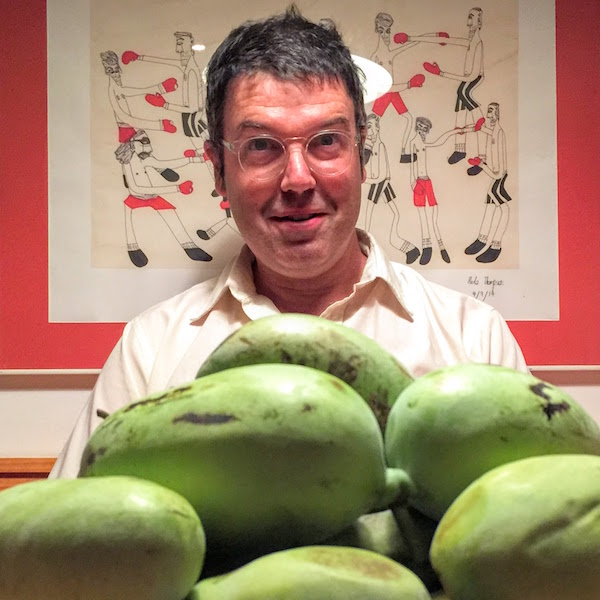 Man seated at table with a large pile of pawpaws.