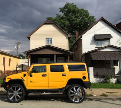 black and gold Hummer in front of single-family frame houses, Arnold, PA