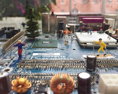 sculpture of tiny skiers on lanscape of recycled circuit board by artist David Martin