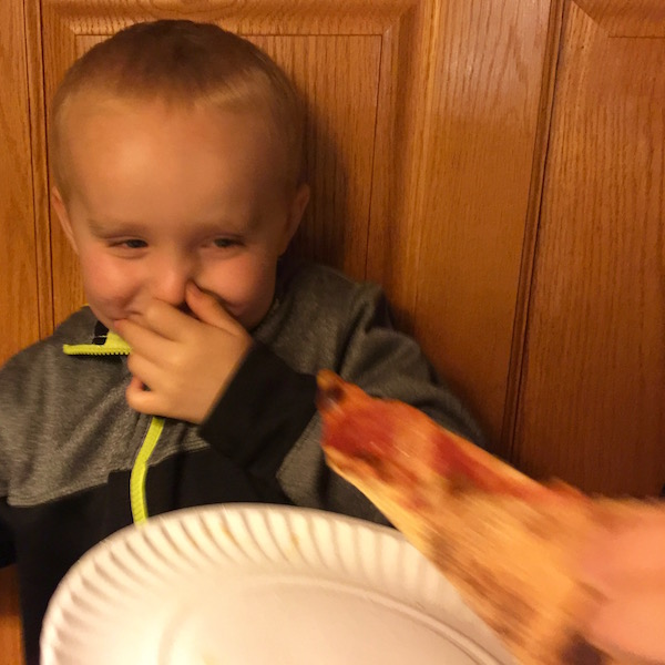 child holding nose as a piece of P&M pizza is offered to him