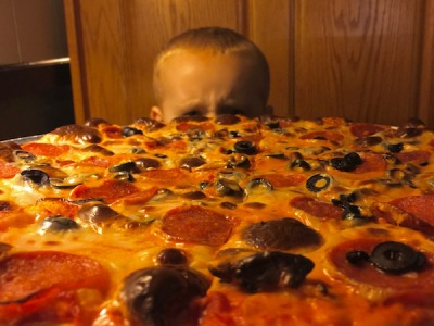 child's head seen over a large pepperoni and olive pizza, P&M Pizza, Arnold, PA