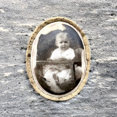 detail from marble headstone with embedded ceramic photograph of baby in high chair, Loretto Cemetery, Pittsburgh, PA