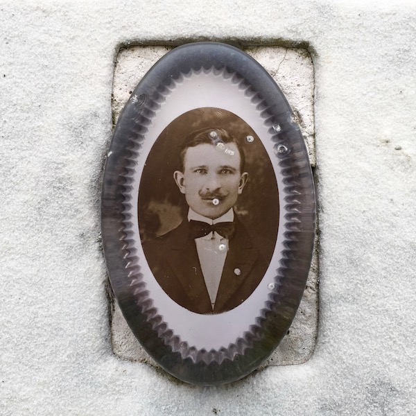 detail of marble headstone with embedded ceramic photograph of middle-aged man encased in plastic, Loretto Cemetery, Pittsburgh, PA