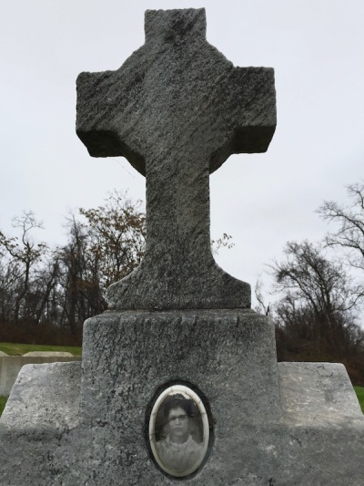 weathered marble headstone in the shape of a cross with embedded ceramic photograph of young woman, Loretto Cemetery, Pittsburgh, PA