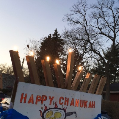 "lit rooftop menorah with homemade ""Happy Chanukah"" sign featuring frying latkes, Pittsburgh, PA"