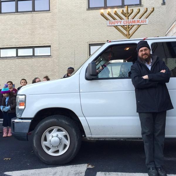 man posing in front of white van with rooftop menorah, Pittsburgh, PA
