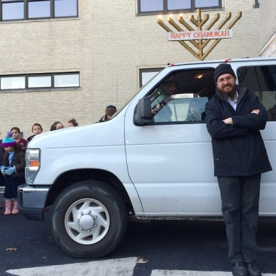 man posing in front of white van with rooftop menorah, Pittsburgh, PA
