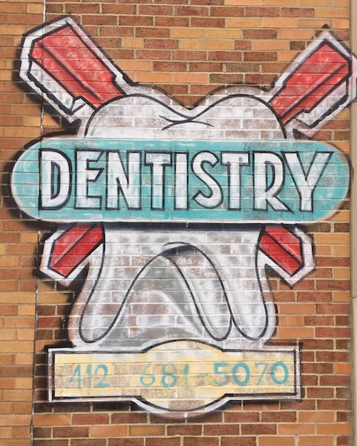 """mural on brick wall of large tooth with crossed toothbrushes and the sign """"Dentistry"""", Pittsburgh, PA"""