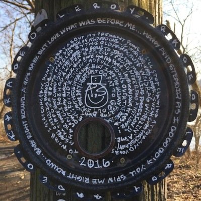 round metal lid painted with long string of text nailed to telephone pole, Pittsburgh, PA