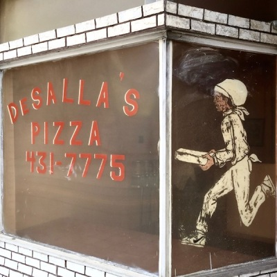 glass storefront windows painted with the name of DeSalla's Pizza and running pizza delivery man, Pittsburgh, PA
