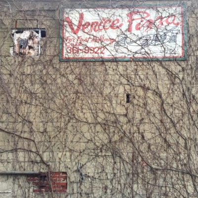 hand-painted sign for Venice Pizza on cinderblock wall, covered in vines, Pittsburgh, PA