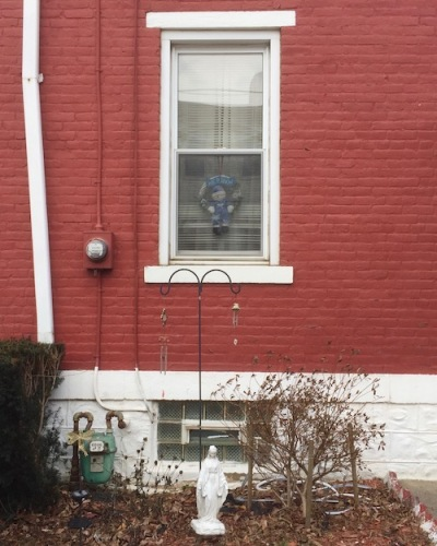 statuette of Mary by red brick rowhouse, Pittsburgh, PA