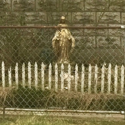 Mary statuette against garage wall behind chain link fence, Pittsburgh, PA