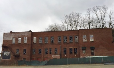 3-story brick former EIS Manufacturing building with broken windows and roof caved-in, Monessen, PA