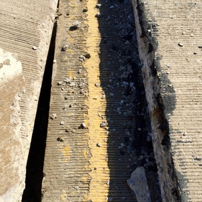 detail of broken road sections showing painted yellow line, Harmar, PA