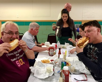 two men eat fish sandwiches in church basement fish fry