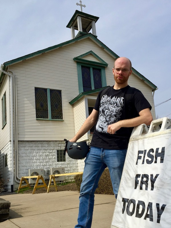 """author Lee Floyd posing on """"Fish Fry Today"""" sign outside church"""