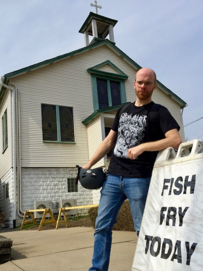 "author Lee Floyd posing on ""Fish Fry Today"" sign outside church"