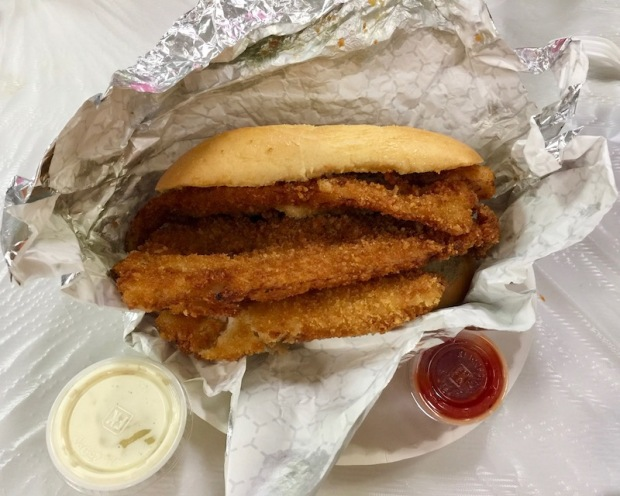 fish sandwich with three breaded fillets of fish from church fish fry