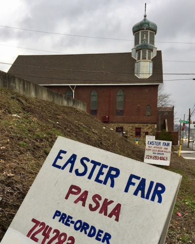side view of St. Michael the Archangel Ukrainian Catholic Church with wooden signs for upcoming Easter fair, Lyndora, PA