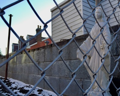 Mary statuette seen through chainlink fence, Pittsburgh, PA
