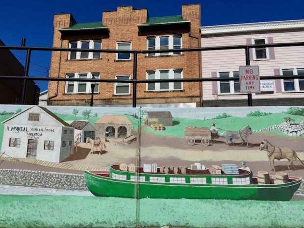 mural of early American settlement with general store, farmers, and river boat, Tarentum, PA